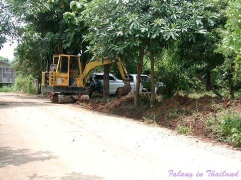Regenzeit in Thailand - Bagger hebt Wassergraben aus