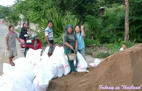Regenzeit in Thailand - Frauen befüllen Sandsäcke