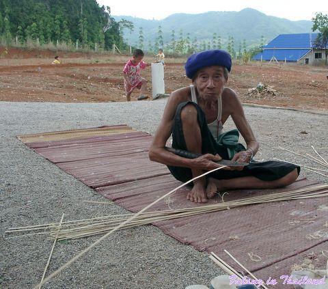 Alter Mann spaltet Bambus