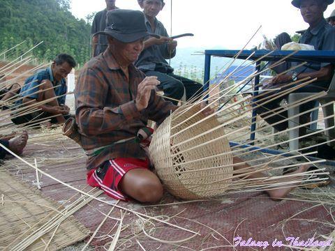 Thailändischer Mann flechtet Bambuskorb